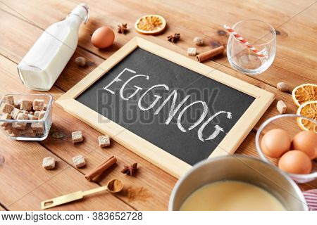 christmas and seasonal drinks concept - eggnog word written on chalkboard, ingredients and aromatic spices on wooden background
