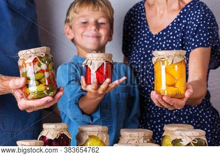 Happy Senior People, Grandmother, Grandfather And Young Boy, Grandson Holding In Hands Jars With Hom