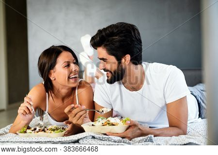 Healthy Breakfast In Bed. Young Beautiful Couple In Love Is Sitting On Bed And Having Breakfast.