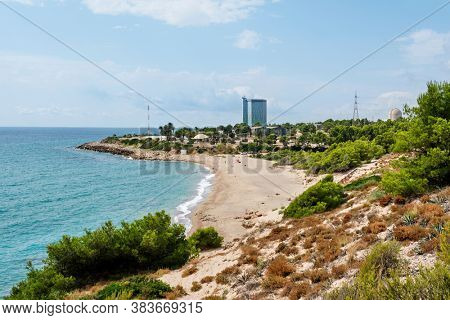 HOSPITALET DEL INFANT, SPAIN - AUGUST 28, 2020: A view over the Cala de Gestell beach in Hospitalet del Infant, Spain, highlighting the Vandellos II nuclear power station in the background