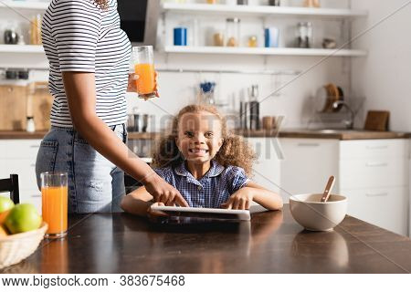 Partial View Of African American Woman In Striped T-shirt Holding Orange Juice And Touching Digital