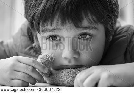 Black And White Photo Of Kid With Bored Face,lonely Boy Putting His Chin Down On Teddy Bear And Look