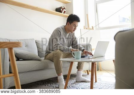 Young Asian Corporate Executive Staying At Home Working Using Laptop Computer