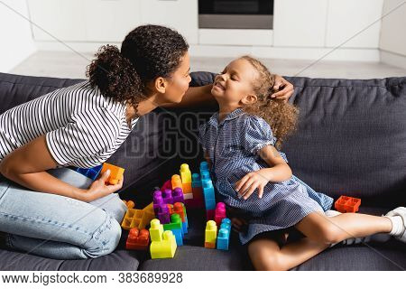 African American Nanny Touching Hair Of Girl While Sitting On Sofa Near Multicolored Building Blocks