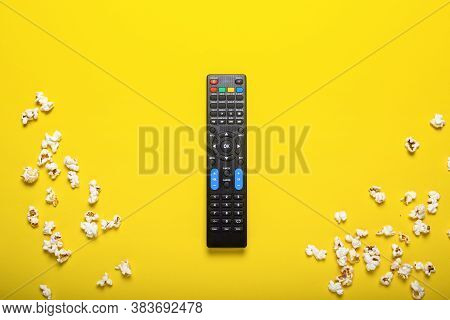 Black Remote Control From A Tv, Tv Tuner Or Audio System On A Yellow Background With Popcorn. Concep