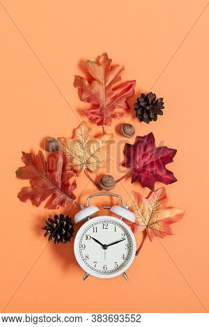 Clock And Leaves Top View On Orange Background. Autumn Time. Daylight Savings Time Concept.