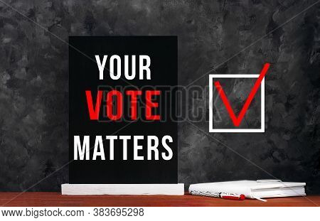 Your Vote Matters Text Sign On Black Chalkboard With White Notebok And Red Pen On Dark Background. M