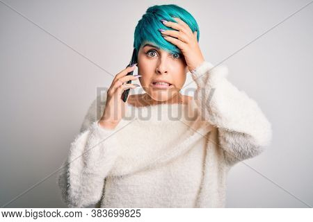 Young woman with blue fashion hair having a conversation talking on smartphone stressed with hand on head, shocked with shame and surprise face, angry and frustrated. Fear and upset for mistake.