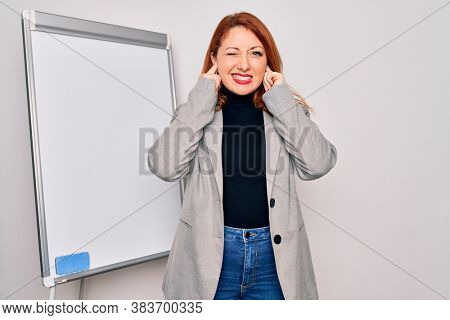 Young beautiful redhead businesswoman doing business presentation using magnetic board covering ears with fingers with annoyed expression for the noise of loud music. Deaf concept.