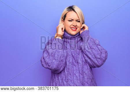 Beautiful blonde plus size woman wearing casual turtleneck sweater over purple background covering ears with fingers with annoyed expression for the noise of loud music. Deaf concept.