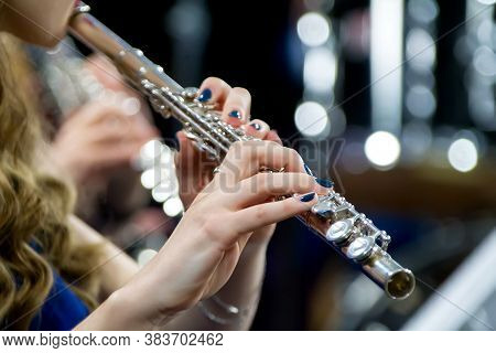 Hands Holding A Flute. Girl Musician Plays The Flute.