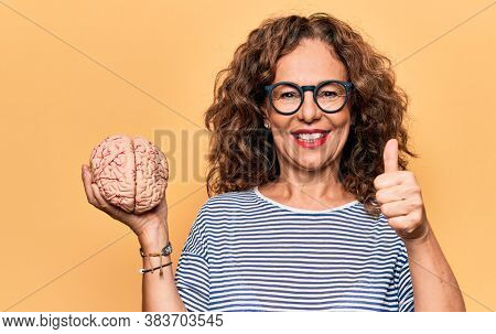 Middle age brunette woman holding brain as mental care and memory health over pink background smiling happy and positive, thumb up doing excellent and approval sign