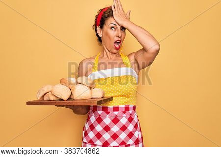 Middle age senior pin up housewife woman wearing 50s style retro dress and apron cooking bread stressed with hand on head, shocked with shame and surprise face, angry and frustrated. Fear and upset.