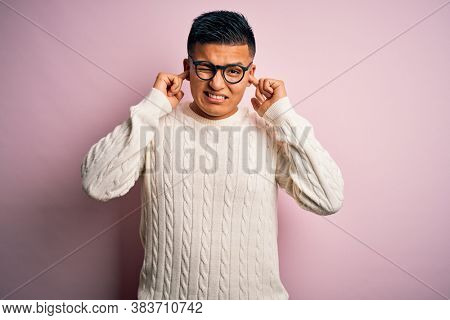 Young handsome latin man wearing white casual sweater and glasses over pink background covering ears with fingers with annoyed expression for the noise of loud music. Deaf concept.