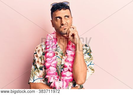 Young hispanic man wearing summer casual clothes thinking concentrated about doubt with finger on chin and looking up wondering