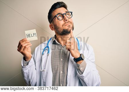 Young doctor man wearing stethoscope holding help note over isolated background serious face thinking about question, very confused idea