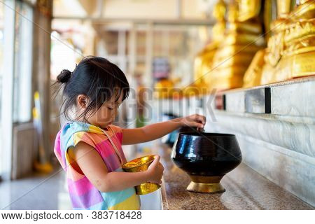 Little Girl Putting Coins In One Of Monk Alms Bowl For Merit In Buddhism With Lots Of Monk Alms Bowl