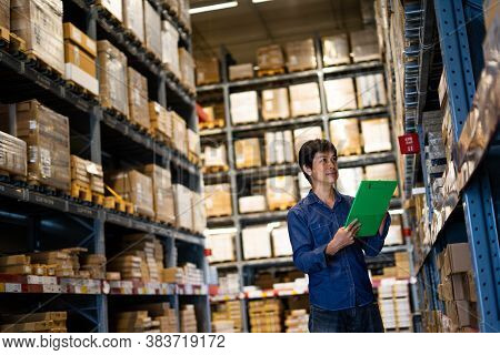 Manager Man Worker Doing Stocktaking Of Product Management In Cardboard Box On Shelves In Warehouse.