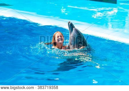 Happy Little Girl Swimming With Dolphins In Dolphinarium