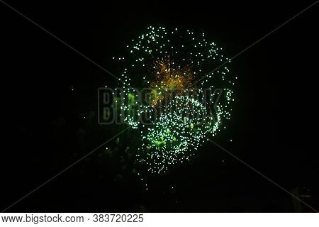 Fireworks In The Sky. Salute Exploded In A Colorful Ball In The Night Sky. Sparks And Lights On A Bl
