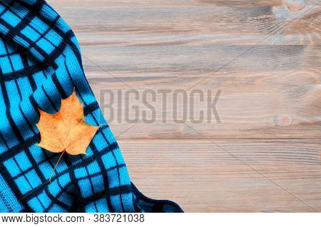 Autumn background - dry autumn maple leaf and blue warm scarf on the wooden background, free space for text. Autumn composition, autumn still life. Colorful autumn background