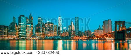 Panoramic View Of New York City Manhattan Midtown At Dusk With Skyscrapers Illuminated Over East Riv