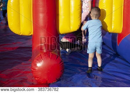Children Frolic On Trampolines. Inflatable Play Area For Children. Fun In The Park. A Child Jumps On