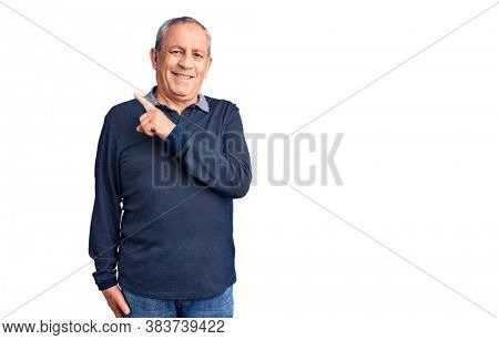 Senior handsome man wearing casual t-shirt cheerful with a smile of face pointing with hand and finger up to the side with happy and natural expression on face