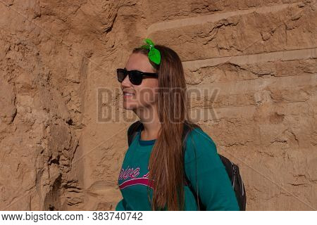 Pretty Hiker Girl With Traveling Backpack Moving Up On The Mountain Road. Smiling Traveler Woman Loo