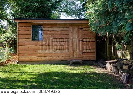 Waney Edge Wooden Rustic Garden Shed Surrounded By Trees.