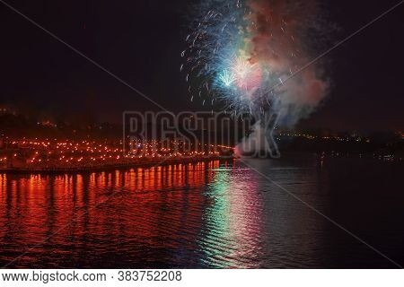 Multi-colors Colorful Fireworks Over The City At Night With Water Reflection. Celebration. Abstract