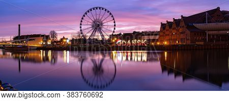Panorama Of Motlawa River And Ferris Wheel With Water Reflection In Old Town Of Gdansk At Night, Pol