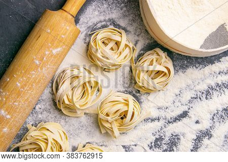 Variety Of Italian Homemade Raw Uncooked Pasta Spaghetti And Tagliatelle With Flour On Wooden Board