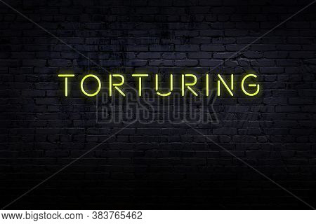 Neon Sign With Inscription Torturing Against Brick Wall. Night View