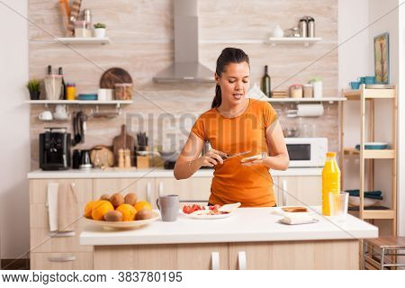 Cheerful Woman In The Morning Singing And Spreading Butter On Roasted Bread. Knife Smearing Soft But