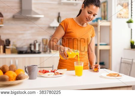 Wife Pouring Fresh Juice In Glass For Breakfast In Kitchen. Woman Drinking Healthy And Natural Orang