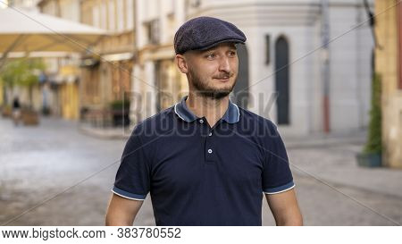 Street Portrait Of A Young Man 30 -35 Years Old In A Cap With A Beard Looking Away On A Neutral Back