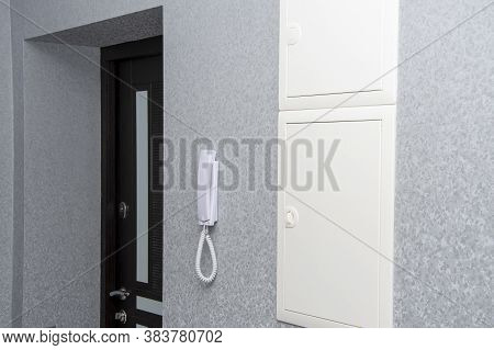 Minimalistic Interior Of The Corridor In The Apartment. An Intercom Is Installed On The Wall In Fron