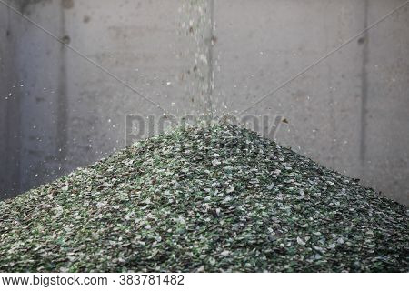 Details With Shards Of Glass Falling From A Conveyor Belt On A Pile In A Glass Recycling Facility.