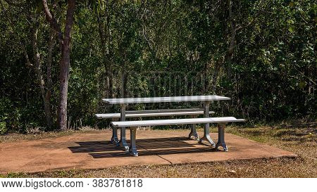A Picnic Table And Seating On A Concrete Pad For Resting Along A Walking Track In Bushland