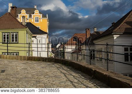 Old Town Street Scene, Or Gamle Bergen, With Houses And Dark Rain Clouds.