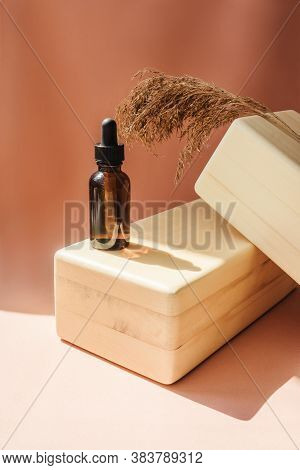 Blank Amber Glass Essential Oil Bottle On Wooden Brick. Natural Organic Cosmetics, Herbal Essence, S