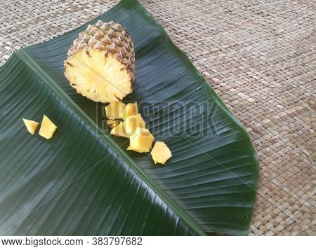 Pineapple And Its Slices Placed In A Green Banana Leaf.