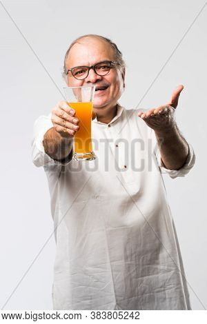 Cheerful Indian Old Man Holding Or Drinking Fresh Orange Or Mango Juice In Glass