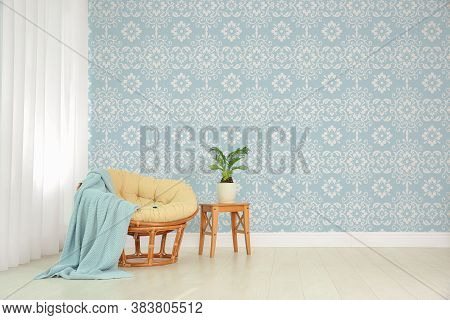 Papasan Chair And Wooden Stand With Houseplant Near Patterned Wallpapers. Interior Design
