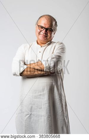 Portrait Of Cheerful Indian Senior Old Man Pointing Or Presenting Or In Hands Folded Pose