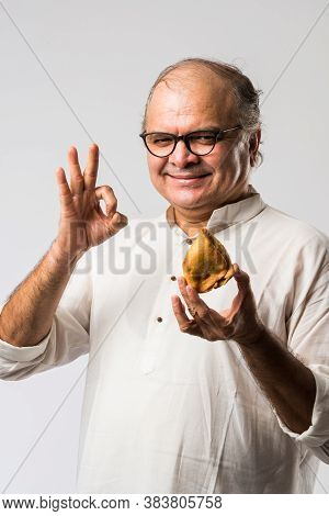 Indian Asian Senior Man Or Old Man Eating Samosa Snack