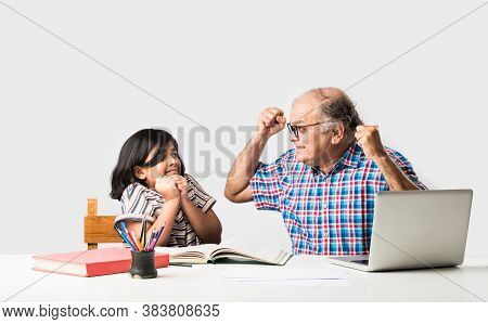 Indian Asian Grandfather Is Teaching His Granddaughter Or Grandaughter At Home