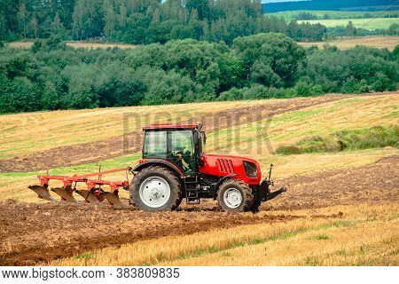 Tractor With Plow, Small Scale Farming With Tractor And Plow In Field. Heavy Agricultural Machinery