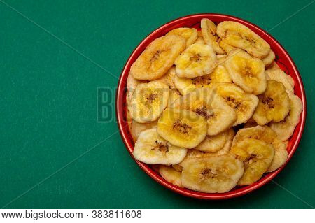 Healthy Snack, Crispy Dehydrated Unsugared Banana Chips In Bowl On Green Background